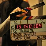 A filmmaker is holding a clapperboard