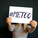 A woman is holding a #metoo placard.